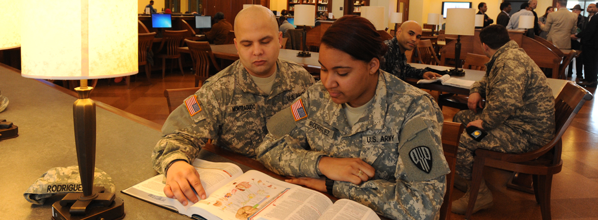 Bronx Community College Veterans Banner with student veterans Rafael Monteagudo (l) and Milissa Rodriguez, US Army in the BCC library