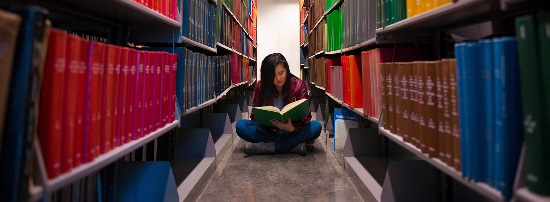 Photo Challenge Winner of student reading in the library stacks, taken by Josue Mendez