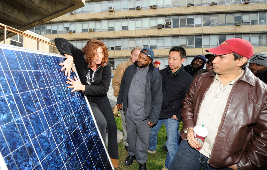 Professor with students and a solar panel, Bronx Community College's Center of Sustainable Energy