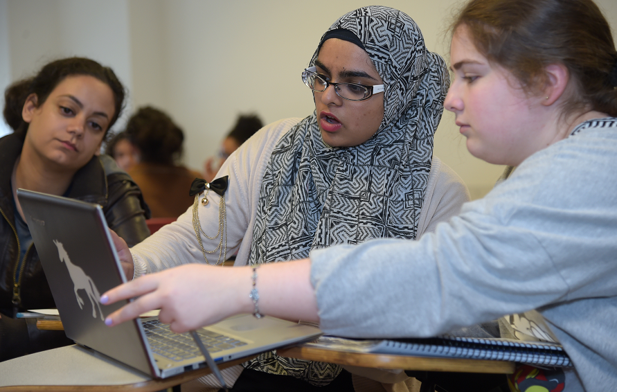 Three female students in class consulting while using a laptop computer