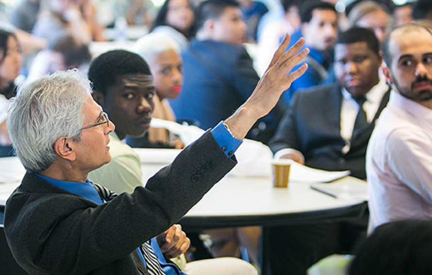Attendee raising his hand to ask a question at the Harvard Consortium
