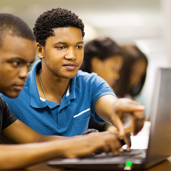 One student helping another on a laptop computer
