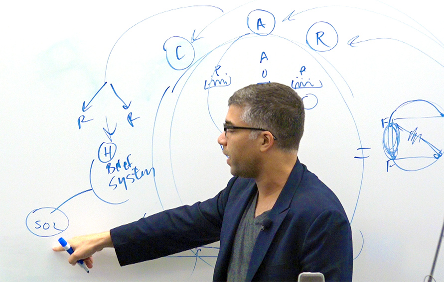 Professor writing on a whiteboard during a CUNY Tech Meetup