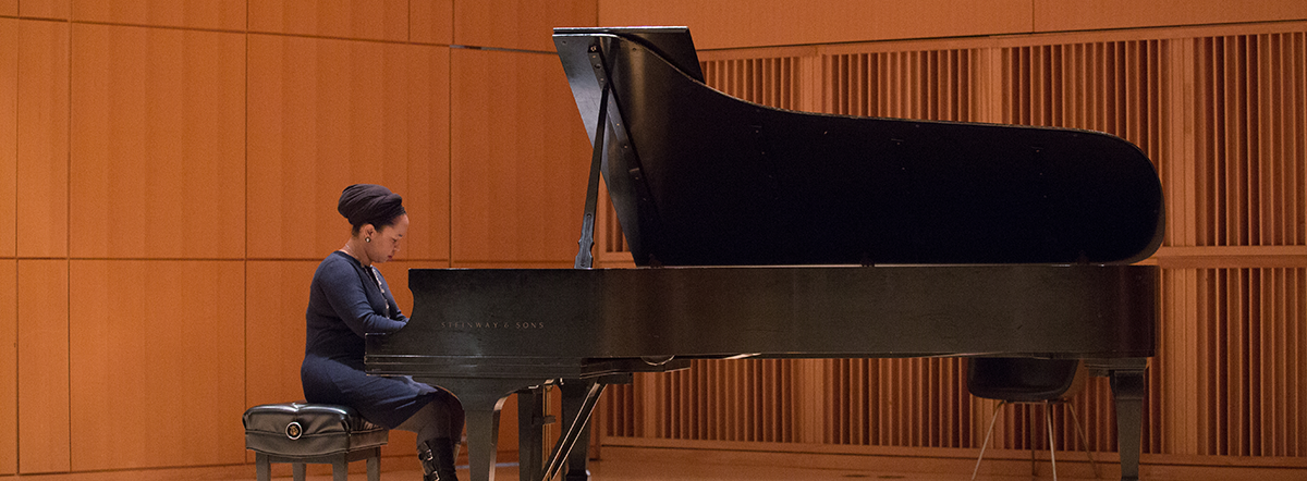 Pianist Courtney Bryan playing piano in the Baisley Powell Elebash Recital Hall at the CUNY Graduate Center