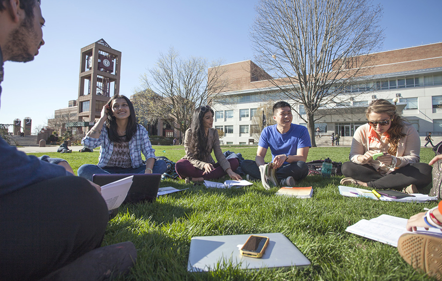 Students sitting outside on the Queens College campus