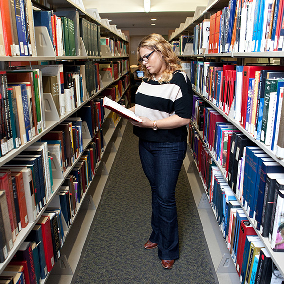 Female student in the library stacks