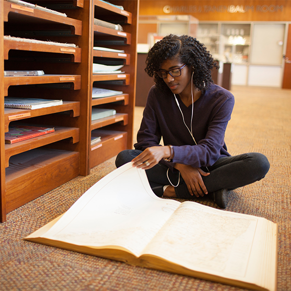 Student studying in the Queens College library