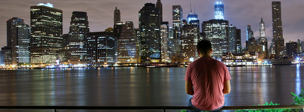 Student sitting at night on the East River facing Manhattan: The Midterm Study, March 2014 Student Photo Challenge winner, silhouetted student in Queens looking across the East River to manhattan at night