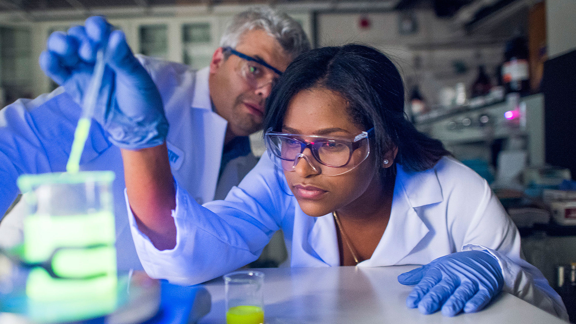 female student in a science lab with a beaker and professor