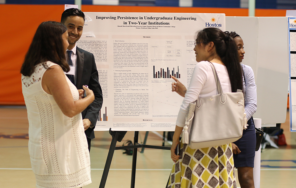 Students viewing poster on community college Engineering education at Hostos Community College.