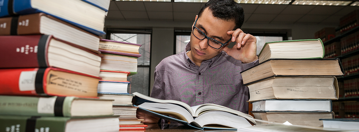 Male student with books in the library