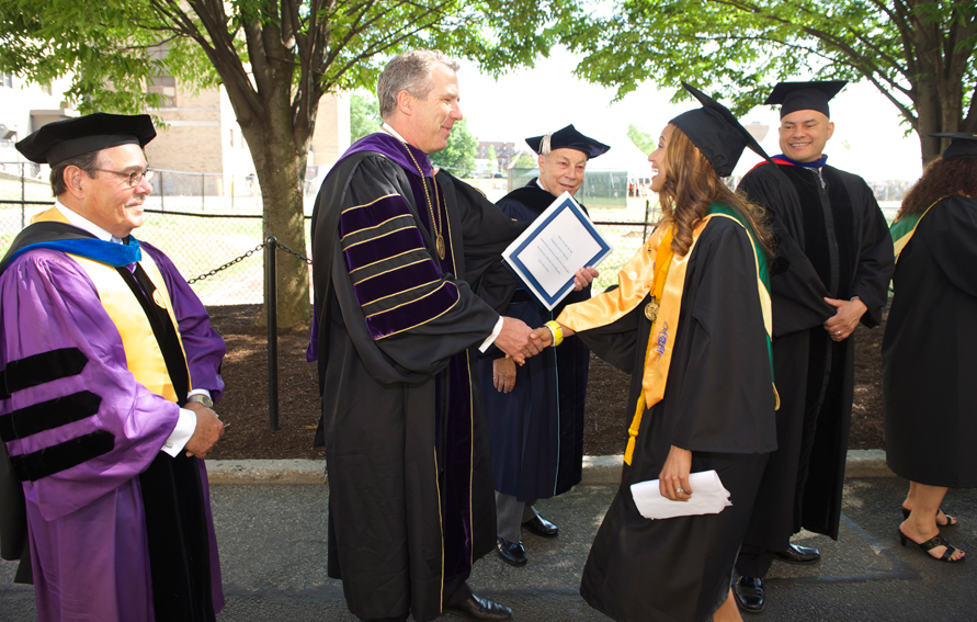 CUNY Chancellor James B. Milliken shaking hands with valedictorian Kirssy Martinez at the 2016 Bronx Community College commencement